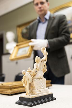 20 cm hög statyett på bord med oskarp person i bakgrunden.