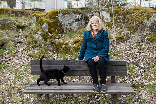 Maria Ohlsson is sitting on her backrest on a park bench and a cat is on her way.